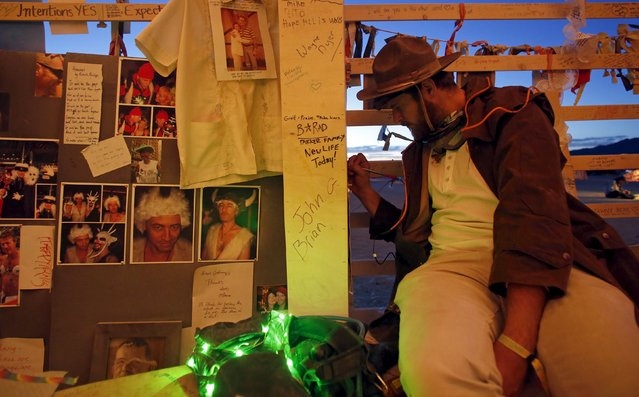 "Andreas Gyr writes a message at the Temple of Promise before sunrise during the Burning Man 2015 ""Carnival of Mirrors"" arts and music festival in the Black Rock Desert of Nevada, September 3, 2015. (Photo by Jim Urquhart/Reuters)"
