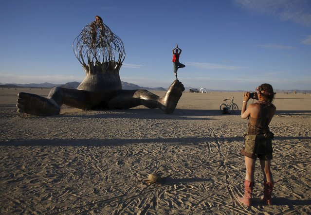 """Kenyon Acton (R) takes a photo of Ian Bennett posing on an art installation during the Burning Man 2015 """"Carnival of Mirrors"""" arts and music festival in the Black Rock Desert of Nevada, September 6, 2015. (Photo by Jim Urquhart/Reuters)"""