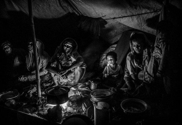 A Rohingya refugee family uses a candle for light as they sit in a makeshift shelter on September 18, 2017 on the roadside after fleeing their village in Myanmar in Cox's Bazar, Bangladesh. (Photo by Kevin Frayer/Getty Images)