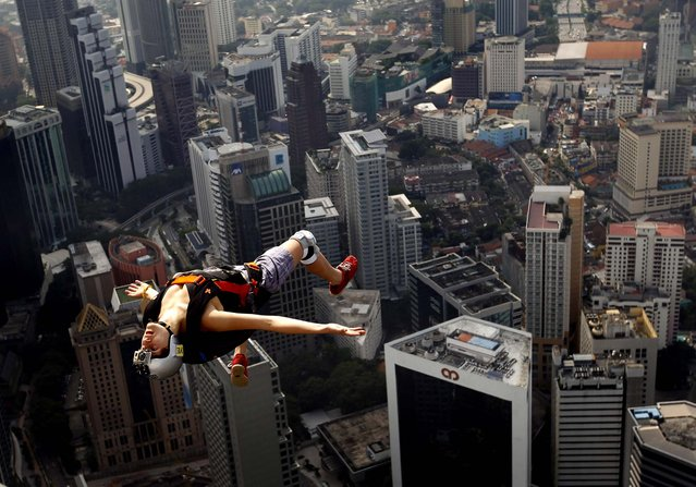 Franch base jumper Florian Pays gestures while leaping from Malaysia's landmark, 1,389-foot high KL Tower in Kuala Lumpur, on September 29, 2012. (Photo by Vincent Thian/Associated Press)