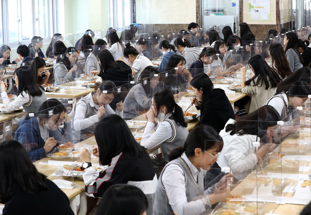 Students sit behind protective screens as a preventative measure against the COVID-19 novel coronavirus as they eat lunch at a high school in Daejeon on May 20, 2020. Hundreds of thousands of South Korean students returned to school on May 20 as education establishments started reopening after a coronavirus delay of more than two months. (Photo by Yonhap/AFP Photo)