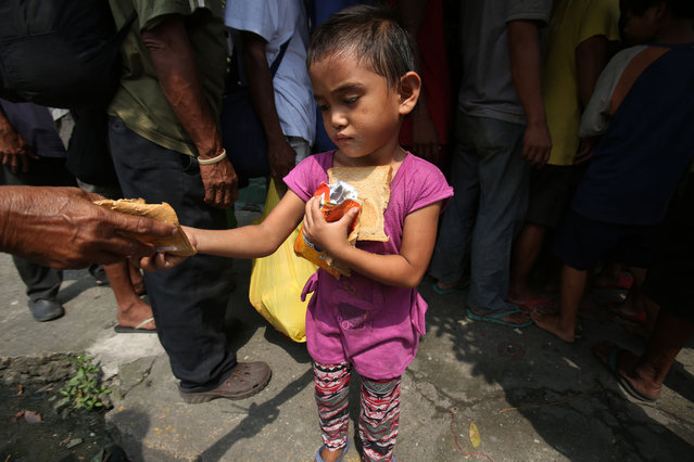 A poor Filipino girl holds bread and drinks she received during a feeding program by Dominican nuns in Manila, Philippines on Wednesday, September 17, 2014. The weekly program gives a free meal to homeless people around the community. (Photo by Aaron Favila/AP Photo)