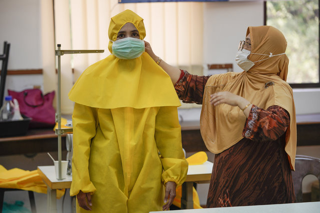 A volunteer tries out a protective suits for health workers, at the International Islamic University Malaysia in Gombak, outskirts of Kuala Lumpur, Malaysia Friday, April 10, 2020. The Malaysian government issued a restricted movement order to the public for the rest of the month to help curb the spread of the new coronavirus. (Photo by Vincent Thian/AP Photo)