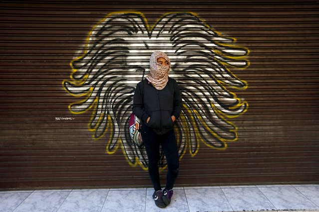 A demonstrator stands in front of graffiti during a protest marking the country's 1973 military coup, in Santiago, Chile September 13, 2015. (Photo by Ivan Alvarado/Reuters)