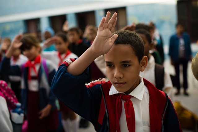 At Manuel Valdes Rodriguez Municipal Primary School in Havana, Cuba, fifth grader, Cristian Gongora, 10, shows his patriotism by saluting the flag and singing the national anthem before going to his classroom in the morning. (Photo by Sarah L. Voisin/The Washington Post)