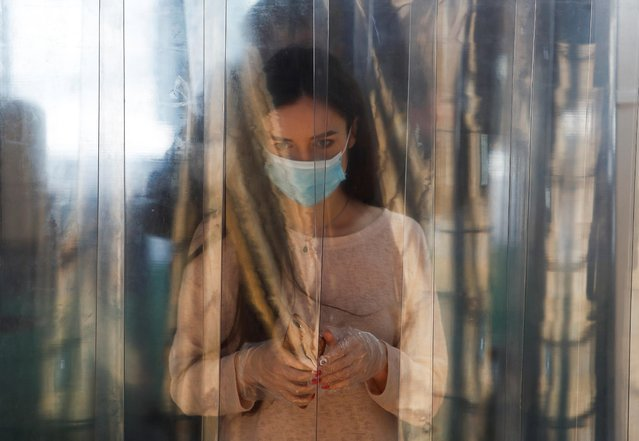 A woman wearing a protective face mask and gloves walks through a disinfection cabin placed at the entrance of the Evropeyskiy shopping mall, after it was reopened as part of a phase of lifting the coronavirus disease (COVID-19) restrictions in Moscow, Russia on June 5, 2020. (Photo by Maxim Shemetov/Reuters)