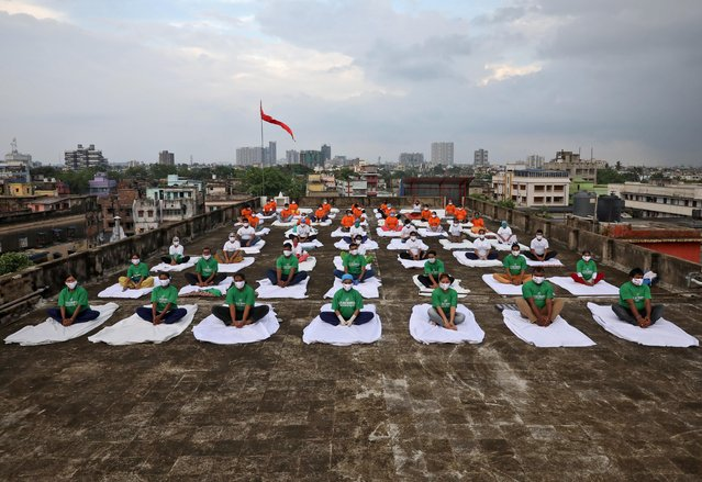 Staff members of a hospital, wearing protective face masks, perform yoga on the rooftop of their hospital building during International Yoga Day, in Kolkata, India, June 21, 2020. (Photo by Rupak De Chowdhuri/Reuters)