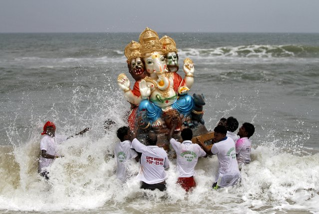 Devotees carry an idol of the Hindu god Ganesh, the deity of prosperity, into the Bay of Bengal for its immersion during the ten-day-long Ganesh Chaturthi festival in Chennai, India, September 20, 2015. (Photo by Reuters/Stringer)