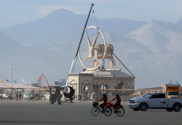 Work continues on the Man as approximately 70,000 people from all over the world gather for the 30th annual Burning Man arts and music festival in the Black Rock Desert of Nevada, U.S. August 29, 2016. (Photo by Jim Urquhart/Reuters)