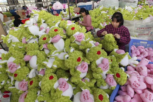 Employees make stuffed toys which they are exporting to Europe and America, at a toy factory in Lianyungang, Jiangsu province October 8, 2014. China's exports rose more than expected in September while imports unexpectedly improved, data showed on Monday, bringing the trade surplus to $31 billion. (Photo by Reuters/China Daily)