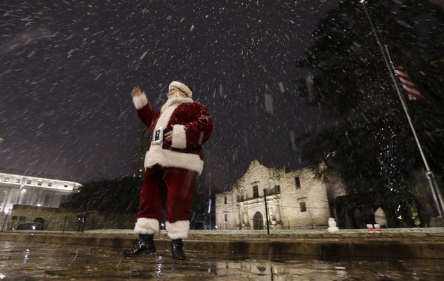 Dressed as Santa Claus, Eldon Hansen stands in front of the Alamo as snow falls in downtown San Antonio, Thursday, December 7, 2017. The National Weather Service said up to 2.5 inches of snow had been measured in the San Antonio area. The most recent comparable snowfall in San Antonio was in January 1987, when 1.3 inches of snow accumulated, but the most recent major snowfall was 13.2 inches in January 1985. (Photo by Eric Gay/AP Photo)