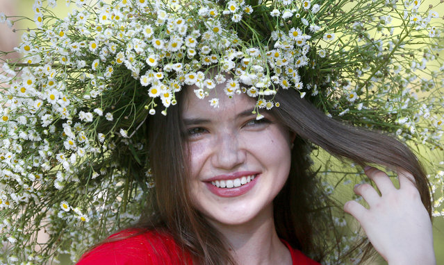 A girl with a ritual garland headdress smiles during a traditional Midsummer Night celebration, in the capital Kyiv, Ukraine, Monday, July 6, 2020. Ukrainian girls believe the ages-old ceremony would help them to find their true love partners, as the pagan Slav festival is still celebrated in Ukraine, as Kyiv has lifted the coronavirus lockdown restrictions. (Photo by Efrem Lukatsky/AP Photo)