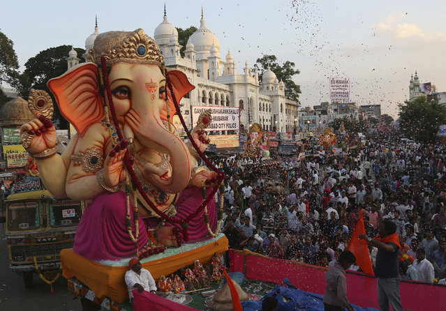Idols of elephant-headed Hindu god Ganesha are taken on trucks in a procession before immersing them in the Hussain Sagar Lake on the final day of the festival of Ganesh Chaturthi in Hyderabad, India, Sunday, September 27, 2015. The immersion marks the end of the ten-day long Ganesh Chaturthi festival that celebrates the birth of the Hindu god. (Photo by Mahesh Kumar A./AP Photo)