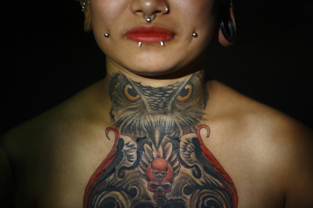 """A tattoo of an owl is pictured on the neck of Jharana Gurung, the first woman from Nepal to perform a body suspension, as she poses for a picture backstage during the """"Nepal Inked – A Tattoo and Lifestyle Convention"""" in Kathmandu October 19, 2014. A total number of 70 artists from Nepal and around the world took part in the three-day convention that ended today. (Photo by Navesh Chitrakar/Reuters)"""