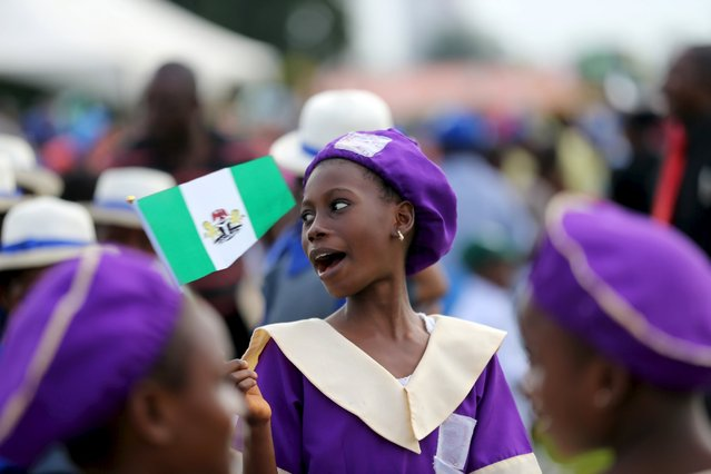 A student holds the Nigerian flag during a parade to commemorate Nigeria's 55th Independence Day in Lagos, October 1, 2015.  REUTERS/Akintunde Akinleye