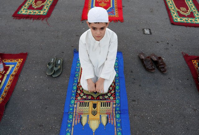 A boy attends Eid al-Adha prayers on the street outside Abu Hanifa mosque in Baghdad Adhamiya district, during the outbreak of the coronavirus disease (COVID-19), in Iraq, July 31, 2020. (Photo by Thaier Al-Sudani/Reuters)