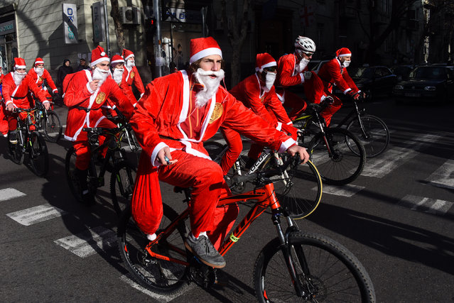 People dressed as Santa Claus ride their bicycles through the streets of Tbilisi on December 28, 2017. (Photo by Vano Shlamov/AFP Photo)