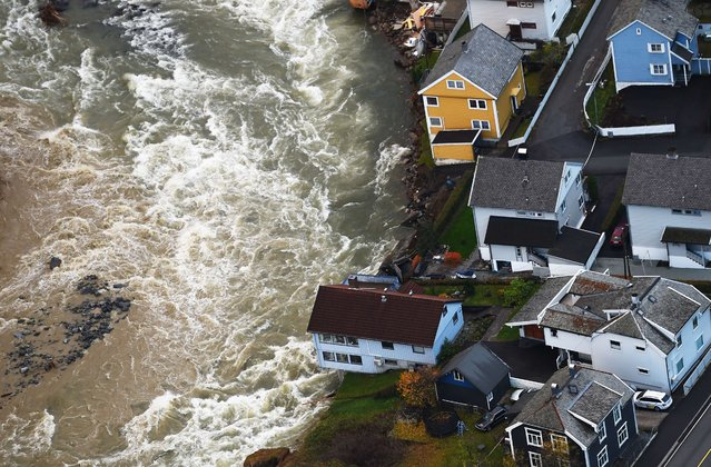 Houses, bridges and roads are damaged by flooding after heavy rain fell in Voss, western Norway on October 29, 2014. Houses have practically been flushed out into the roaring rivers. The cultural center of the community is situated on the banks of the river Opo in Voss. (Photo by Marit Hommedal/AFP Photo)
