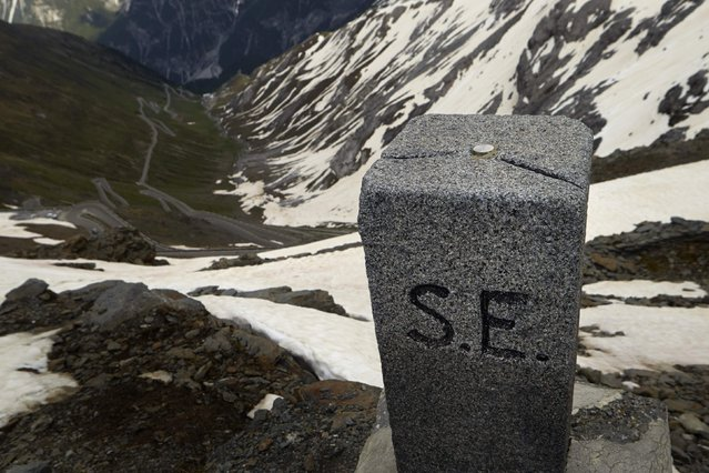 A marker stands at the Dreisprachenspitze (Three Languages Peak) in front of the road to the Stelvio Pass at the border between Italy (R) and Switzerland in Tschierv May 13, 2014. German, Italian and Romansh speaking areas meet at Dreisprachenspitze. (Photo by Denis Balibouse/Reuters)