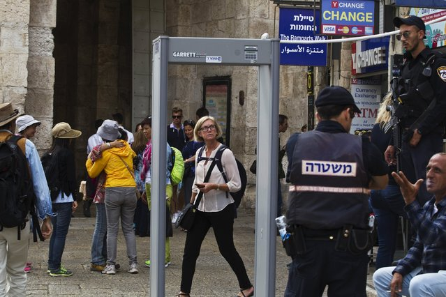 "A woman looks at a newly erected metal detector in Jerusalem's Old City October 8, 2015. A spate of ""lone-wolf"" stabbing attacks has alarmed authorities and unsettled Israelis, with Jerusalem's mayor urging people with gun licenses to carry their weapons and Israeli leaders vowing to quash the violence though apparently stumped over how to do so. (Photo by Ronen Zvulun/Reuters)"