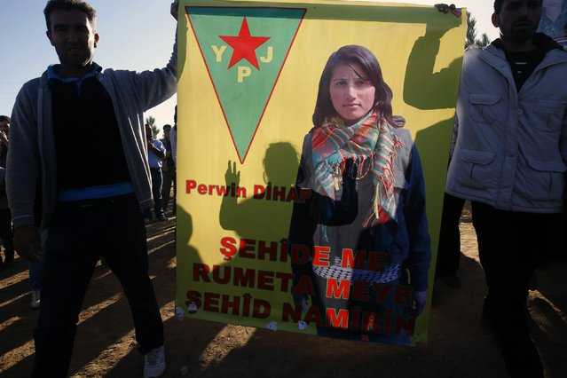 Kurdish mourners hold up a poster of Perwin Mustafa Dihap, a 19-year-old fighter with the YPJ (Women's Protection Force), during a funeral ceremony for two female Kurdish fighters killed during the battle for Kobani against Islamic State militants, in a graveyard in the Turkish border town of Suruc, Sanliurfa province November 7, 2014. (Photo by Yannis Behrakis/Reuters)
