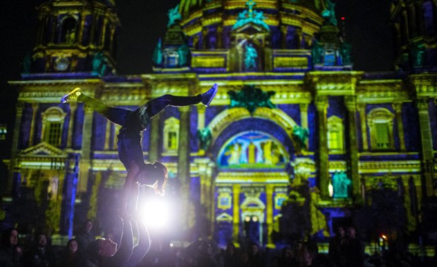 "Athletes perform in front of a light installation at the Berlin Cathedral during the opening day of the ""Festival of Light"" show in Berlin, Germany, October 9, 2015. (Photo by Hannibal Hanschke/Reuters)"