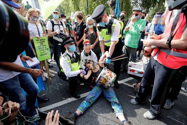 """Police officers wearing face masks and gloves due to the COVID-19 pandemic, detain an activist from the climate protest group Extinction Rebellion as they demonstrate in Parliament Square in London on September 2, 2020, on the second day of their new season of """"mass rebellions"""". Climate protest group Extinction Rebellion will target Britain's parliament as part of """"mass rebellions"""" starting from September 1. Other actions will take place around the country. (Photo by Tolga Akmen/AFP Photo)"""
