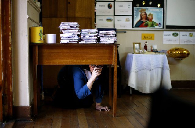 A teacher takes cover under her desk inside a school during an earthquake drill in Santiago, November 13, 2014. (Photo by Ivan Alvarado/Reuters)
