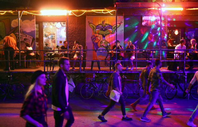 People walk through the RAW area in Berlin, Germany, September 3, 2016. Night after night thousands of Berliners and visitors head to hotspots like RAW, an old graffiti-covered train-repair site in the eastern part of the city that was once under Communist rule but is now home to clubs, bars and a pool replete with beer garden. (Photo by Hannibal Hanschke/Reuters)