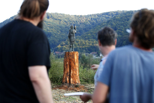 Local people look at a bronze statue representing the U.S first lady Melania Trump made by Brad Downey, a Berlin-based U.S. artist, is erected in her birthplace of Sevnica, Slovenia, Tuesday, September 15, 2020, after a previous one, made in wood, was set alight. Melania Trump was born and grew up in Slovenia before moving abroad as a fashion model. (Photo by AP Photo/Stringer)