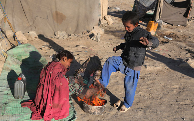 Afghan children warm themselves by a fire on a street in Ghazni on November 21, 2014, the day after Universal Children's Day. Universal Children's Day takes place annually on November 20. (Photo by Rahmatullah Alizadah/AFP Photo)