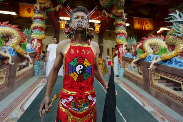A devotee of the Chinese Ban Tha Rue shrine walks with spikes pierced through his cheeks during a procession celebrating the annual vegetarian festival in Phuket, Thailand, October 17, 2015. (Photo by Jorge Silva/Reuters)