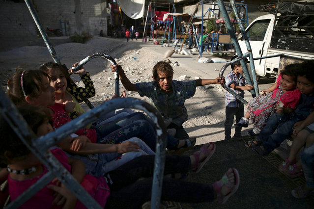 Children play on the last day of Eid al-Adha celebrations in the rebel held besieged town of Hamouriyeh, eastern Ghouta, near Damascus, Syria September 15, 2016. (Photo by Bassam Khabieh/Reuters)