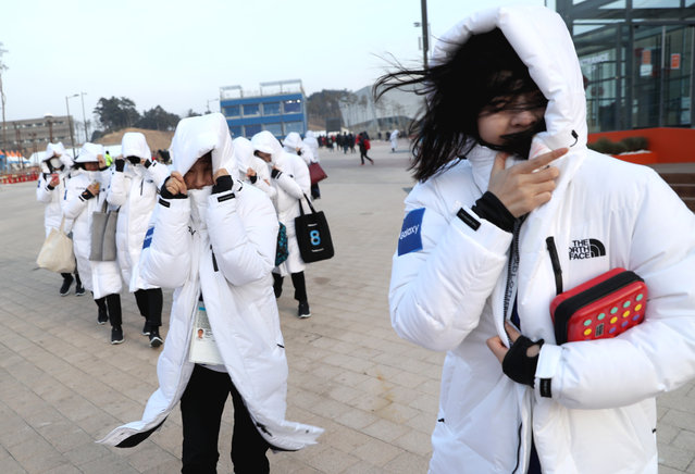 Staff from Gangneung Olympic Park protect themselves from strong winds as they leave Gangneung Olympic Park during the Pyeongchang 2018 Winter Olympic Games in Pyeongchang on February 14, 2018. (Photo by Damir Sagolj/Reuters)