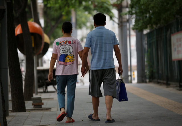 Wang and her husband Liu hold hands as they walk toward a hospital in Beijing, China, June 23, 2016. Wang, who suffers from cervical cancer, came from Inner Mongolia to seek treatment at a specialist hospital in Beijing. (Photo by Kim Kyung-Hoon/Reuters)
