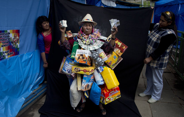 "In this February 3, 2018 photo, fair vendors hold up a black backdrop behind Alberto Macias Rios, dressed as ""Ekeko"", the god of prosperity and the central figure of the Alasita Fair, as he poses for a picture in La Paz, Bolivia. Macias, 65, says his low stature helps him pull off the Ekeko personality. ""I grew up with the Alasitas fair accompanying my mother when the fair filled various streets and avenues of La Paz"", he said. Macias competed in this year's Ekeko costume competition. (Photo by Juan Karita/AP Photo)"