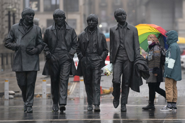 """Members of the public wearing face masks stand near a statue of The Beatles in Liverpool, England, Monday October 12, 2020, as Prime Minister Boris Johnson prepares to lay out a new three-tier alert system for England. The Liverpool City Region is expected to face the tightest restrictions under the new system, which will classify regions as being on """"medium"""", """"high"""" or """"very high"""" alert. (Photo by Jon Super/AP Photo)"""