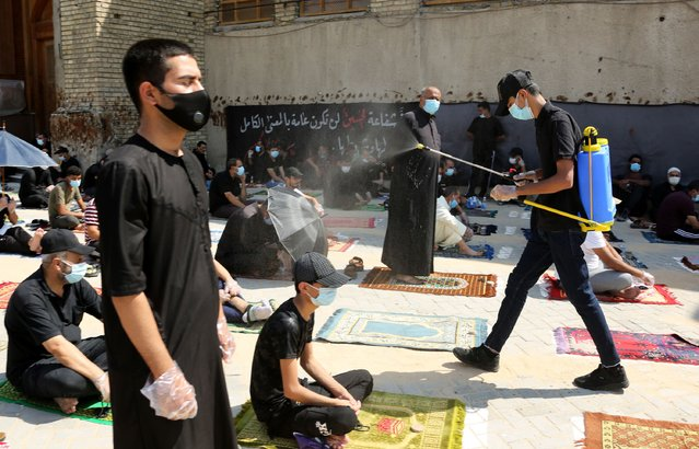 A medical personnel sprays disinfectant as Iraqi Shiite worshipers perform their Friday Prayers amid the spread of COVID-19 in Sadr City, the Shiite stronghold of northeastern Baghdad, Iraq, 25 September 2020. Iraqi authorities have now allowed the reopening of mosques, restaurants, cafes, parks, malls and canceled the overnight curfews, as the country eases the restrictions it had imposed in a bid to stem the spread of the ongoing pandemic of the COVID-19 disease caused by the SARS-CoV-2 coronavirus. (Photo by Ahmed Jalil/EPA/EFE/Rex Features/Shutterstock)