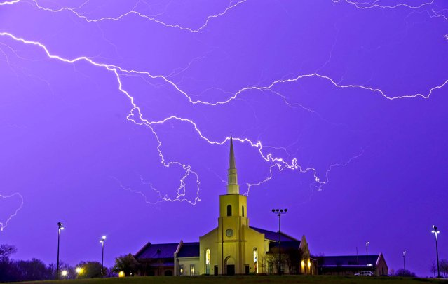 Lightning steaks across the sky behind the Young Meadows Presbyterian Church in Montgomery, Ala., Monday, March 18, 2013. Strong storms moved across much of Alabama on Monday, bringing hail, high winds, and heavy rainfall as a cold front passed through the state. (Photo by Dave Martin/AP Photo)