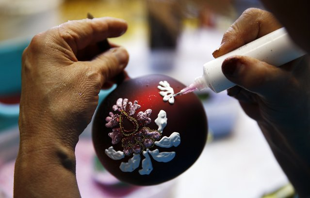 A worker paints Christmas decorations on glass baubles at the Silverado manufacture of hand-blown Christmas ornaments in the town of Jozefow outside Warsaw December 2, 2014. (Photo by Kacper Pempel/Reuters)