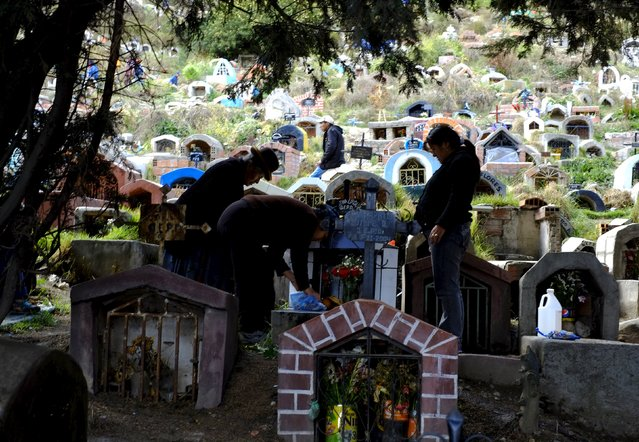 "Silhouetted  members of a family attend to a grave at ""Las LLamitas"" cemetery during the ""All Saints Day"" celebrations in La Paz, Bolivia, November 1, 2015. (Photo by David Mercado/Reuters)"