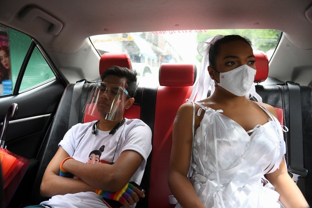 Transgender drag queen Aunchalee Pokinwuttipob, better known by the stage name, Angele Anang, 26, travels in a taxi with her friend Chakkrai Jermkwan as they head to a rally against Prime Minister Prayuth Chan-ocha and to call for reforms to the monarchy, in Bangkok, Thailand, September 19, 2020. (Photo by Chalinee Thirasupa/Reuters)