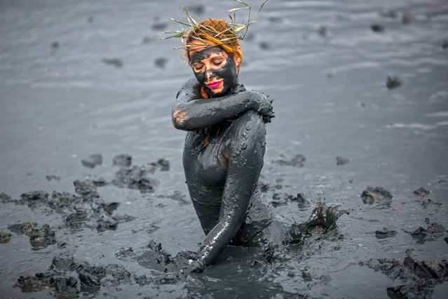 "A woman smears mud on during the ""Bloco da Lama"", a mud carnival party, in Paraty, Rio de Janeiro state, Brazil, on February 22, 2020. ""Bloco da Lama"" started in 1986 with teenagers playing with mud and became a traditional event at the historical city of Paraty. (Photo by Daniel Ramalho/AFP Photo)"