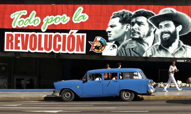 A 1956 Chevrolet car used as a taxi is parked in front of a mural celebrating a Union de Jovenes Comunistas (Young Communists Union) congress in Havana, April 4, 2010. (Photo by Enrique De La Osa/Reuters)