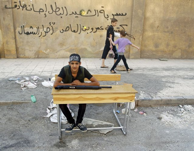 """A young Free Syrian Army fighter rests on a school bench on a street in downtown Aleppo August 2, 2012. The graffiti behind him shows the name of the brigade: """"Ihsan Sadiq fighting group, Amr bin al-Aas brigade of the Free North"""". (Photo by Goran Tomasevic/Reuters)"""