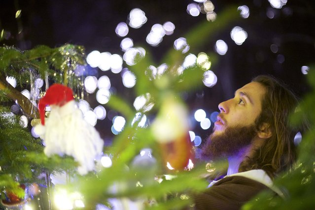 "Michael Grant, 28, ""Philly Jesus"", adjusts Christmas ornaments with his walking staff at Rittenhouse Park in Philadelphia, Pennsylvania December 14, 2014. (Photo by Mark Makela/Reuters)"