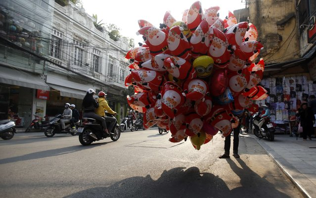 A man sells Santa Claus shaped balloons on a street in Hanoi December 23, 2014. (Photo by Reuters/Kham)