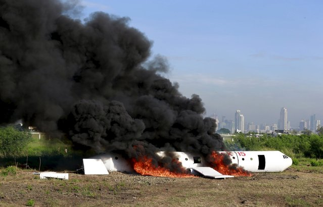 A mock aircraft is covered by fire and smoke during a Crash and Rescue Exercise (CREX) at the  runway of Ninoy Aquino International Airport Terminal 3 in Pasay city, metro Manila November 12, 2015. According to the organizer, the annual drill is part of the Manila International Airport Authority's preparedness exercise aimed at improving its security standards in compliance with the Civil Aviation Organization. (Photo by Romeo Ranoco/Reuters)