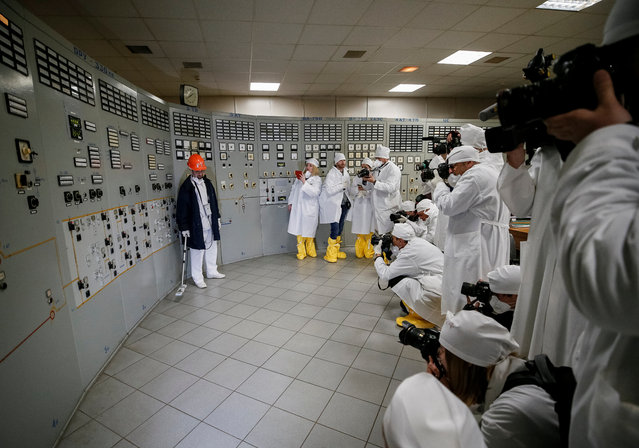 An employee measures the radiation level as journalists take pictures at a control centre of the stopped third reactor at the Chernobyl nuclear power plant in Chernobyl, Ukraine April 20, 2018. (Photo by Gleb Garanich/Reuters)
