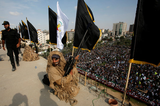 Palestinian Islamic Jihad militant takes up a position on a roof  during a rally marking the 29th anniversary of the movement foundation in Gaza City October 21, 2016. (Photo by Suhaib Salem/Reuters)